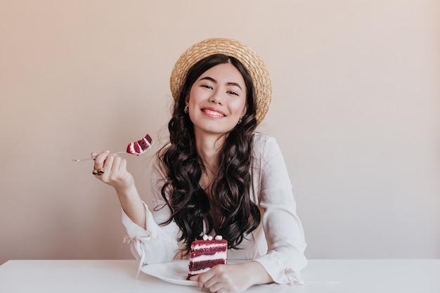 ケーキを食べるゴージャスなアジアの女性。デザートを楽しんでいる笑顔の誕生日の女性。