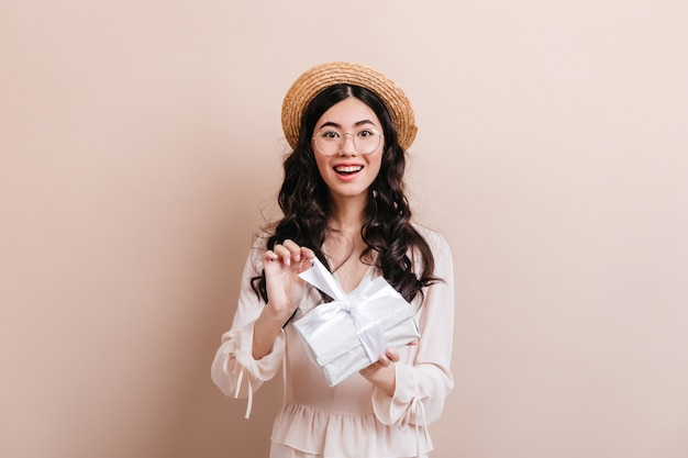 Gorgeous asian woman opening birthday present. front view of glad korean woman with gift.