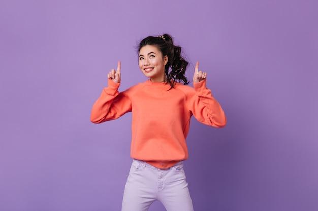 손가락으로 가리키는 웃 고 화려한 아시아 여자. 보라색 배경에 몸짓 행복 한 일본 젊은 여자.