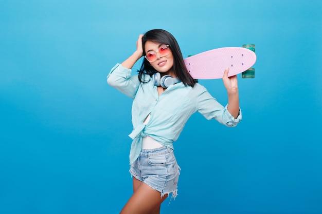 ストレートヘアのゴージャスなアジアの女性は、明るいインテリアの部屋でスケートボードでポーズをとるデニムのショートパンツを着ています。かわいいサングラスを楽しんで自信を持ってヒスパニック系の女の子の肖像画。