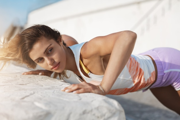 Gorgeous athletic sporty woman push-up looking aside motivated, setting goal during productive morning exercise