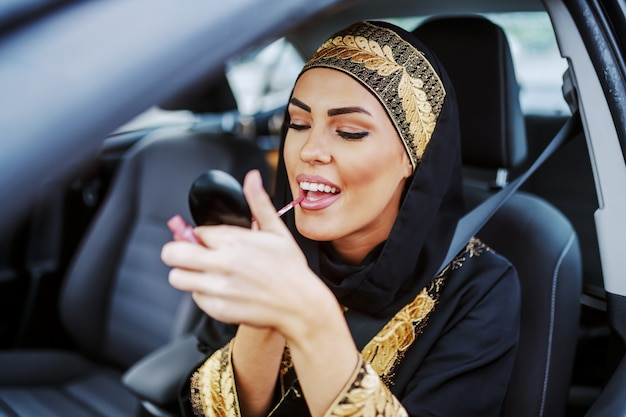 Gorgeous attractive young muslim woman in traditional wear sitting in her car during traffic jam and putting on lipstick.