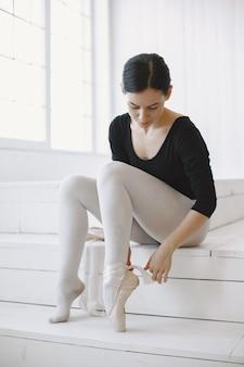 ゴージャスなバレエダンサー。ポワントとバレリーナ。白い壁の女の子。