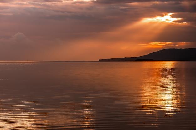 穏やかな海を照らす雲の後ろから出てくる豪華な太陽光線