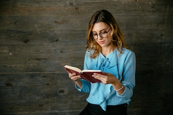 Gorgeous beautiful clever woman in eyeglasses reading interesting book, looks pensive
