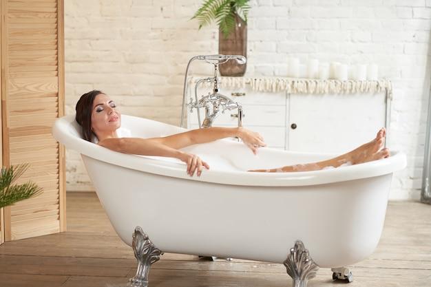 ゴージャスな美しい女性がお風呂に入ります。泡風呂でリラックス。