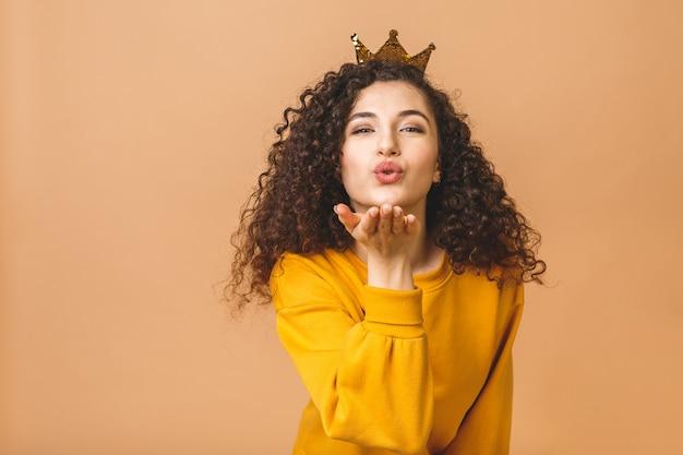 Шикарная красивая девушка с курчавыми коричневыми волосами и носить вскользь и держа крону на голове изолированной над бежевой предпосылкой студии. посылаю воздушный поцелуй.