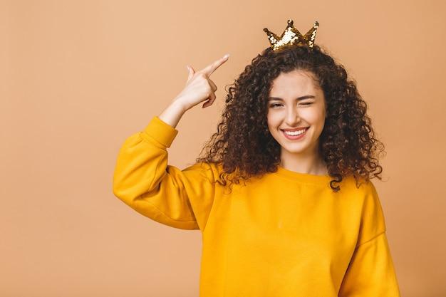 Шикарная красивая девушка с курчавыми коричневыми волосами и носить вскользь и держа крону на голове изолированной над бежевой предпосылкой студии.