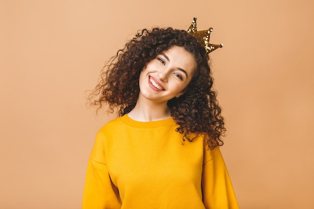 Gorgeous beautiful girl with curly brown hair and wearing casual and holding crown on head isolated over beige studio background.