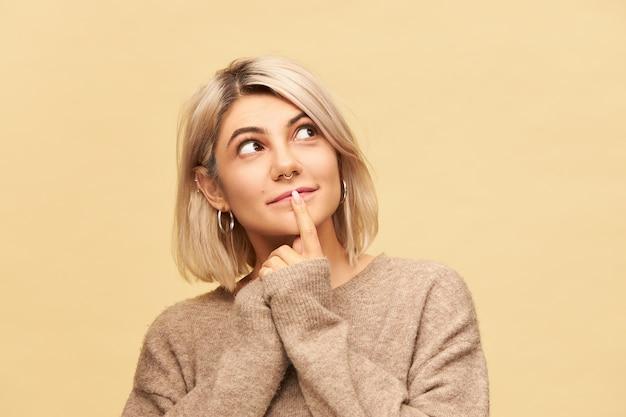 特大のカシミヤのプルオーバーに身を包んだゴージャスな美しい若い女性は、好奇心旺盛な興味のある表情を見上げ、唇に前指を持って、笑っています。ボディランゲージ
