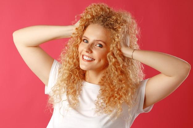 カメラでポーズをとる巻き毛のゴージャスな美しい若い女性のクローズアップ