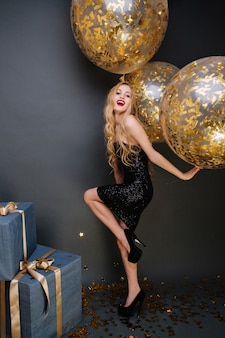 金色の見掛け倒しでいっぱいの大きな風船を楽しんでいる長い巻き毛のブロンドの髪を持つゴージャスな美しい若い女性。豪華なドレス、誕生日パーティー、プレゼント、幸せを祝います。
