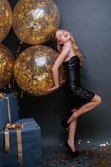Splendida bella giovane donna con lunghi capelli biondi ricci, sui tacchi, vestito di lusso nero che esprime emozioni positive. celebrare la festa di compleanno, divertirsi, regali, felicità.