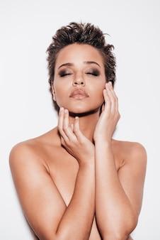 Великолепная красота. красивая молодая женщина без рубашки, прикрывая грудь руками и касаясь лица, держа глаза закрытыми и стоя на белом фоне
