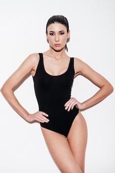 Великолепная красота. красивая молодая женщина в черном купальнике, взявшись за руки на бедрах и глядя в камеру, стоя на белом фоне