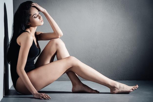 ゴージャスな美しさ。灰色の背景に対して床に座っている間目を閉じて髪を手に保つ黒い水着の美しい若いアフリカの女性の側面図