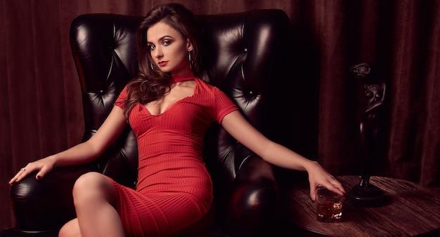 가죽 의자에 화려한 아름다움 젊은 갈색 머리 여자