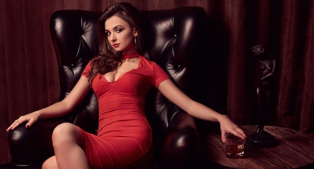 Gorgeous beauty young brunette woman in a leather chair