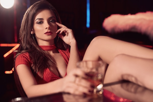 Gorgeous beauty young brunette woman in red dress with glass of whiskey