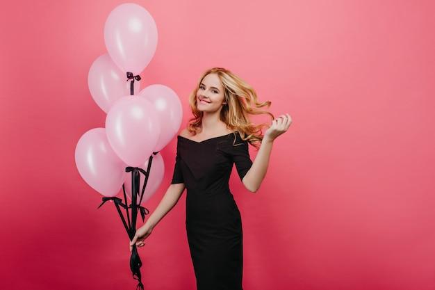 ゴージャスな誕生日の女の子は彼女の明るい髪で遊ぶ。ヘリウム気球でポーズをとる長いドレスを着た魅力的な金髪の女性の屋内写真。