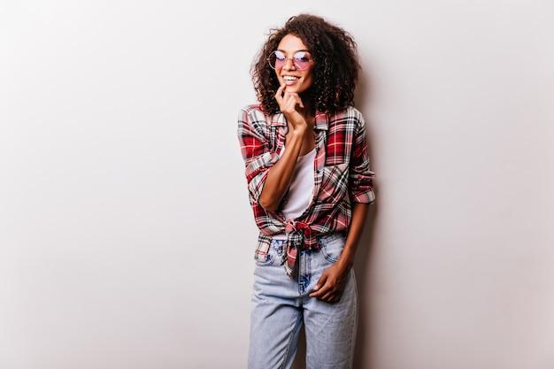 웃 고 빈티지 청바지에 화려한 흑인 여성 모델입니다. 쾌활 한 아프리카 여자의 초상화는 빨간 체크 무늬 셔츠를 입는다.