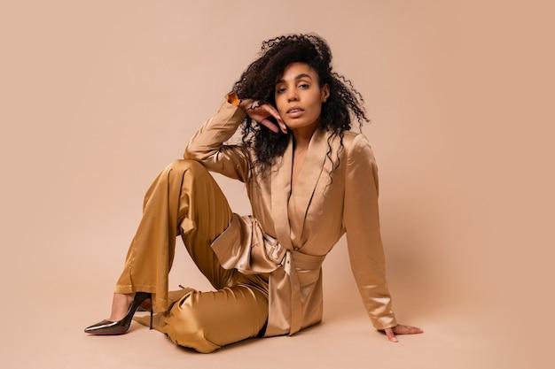 베이지 색 벽에 포즈 우아한 황금 새틴 정장에 아름 다운 물결 모양의 머리카락과 화려한 흑인 여성. 봄 패션 봐.
