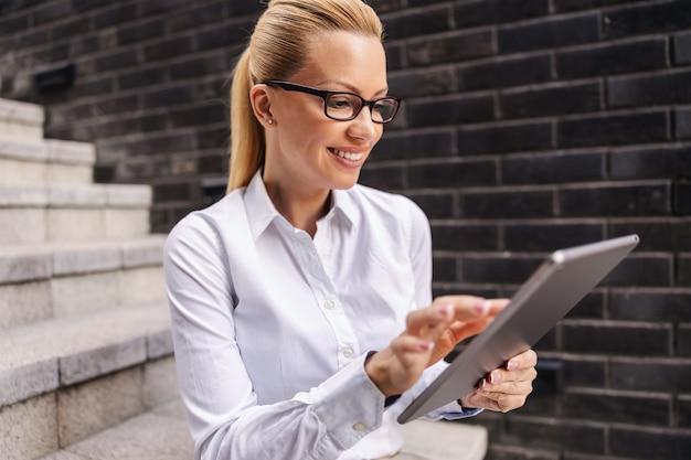 屋外の階段に座ってタブレットを使用してゴージャスな金髪のファッショナブルな笑顔の実業家。