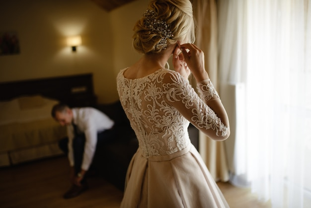 Gorgeous, blonde bride in a white luxurious dress getting ready for the wedding