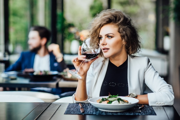 레드 와인 한 잔을 곁들인 화려한 금발 비즈니스 여성 프리랜서는 고급 레스토랑에서 저녁 식사를 합니다.