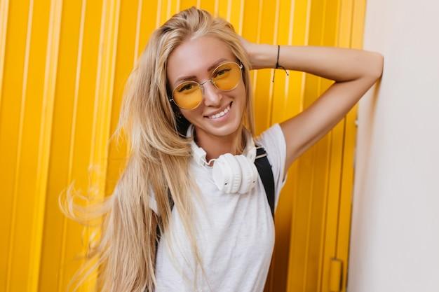 黄色い柵の近くで自信を持って笑顔でポーズをとるゴージャスな金髪の女性モデル。