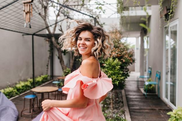 屋外カフェで踊るゴージャスなブロンドの女の子。街で幸せを表現する日焼けした肌を持つ素晴らしい笑顔の女性の肖像画。