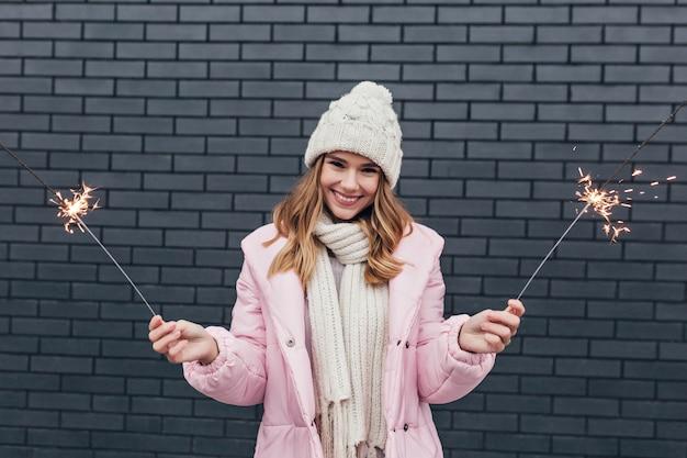 Splendida ragazza bionda in cappello lavorato a maglia che esprime felicità e posa con luci bengala. ridendo la donna bianca in cappello celebraing natale.