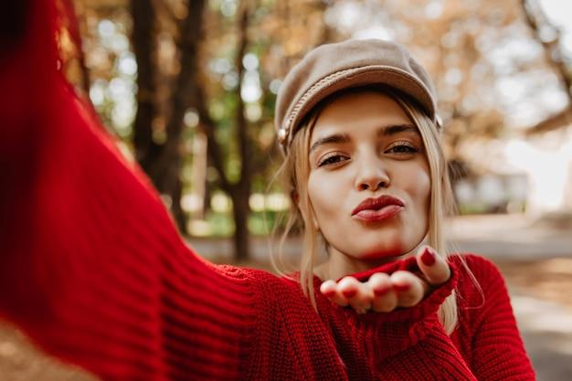 ゴージャスなブロンドの女の子が公園で自分撮りにキスをします。素敵な女性はスタイリッシュな赤いセーターと軽い帽子をかぶっています。