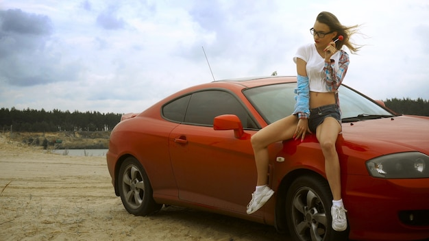 Gorgeous blonde in glasses sits on a red car with lollipop in her hands at the seashore