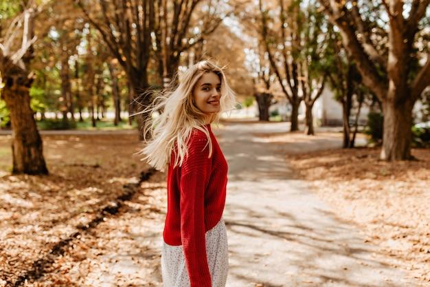 美しい公園で楽しい時間を過ごしているゴージャスなブロンド。黄色の葉の間でふざけて笑っているかわいい女の子。