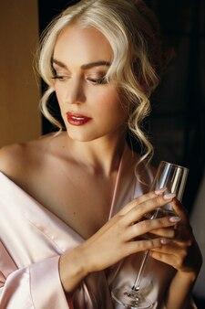 Великолепная блондинка держит в своих тонких пальцах шампанскую флейту