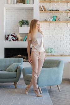 큰 창과 장식 벽이있는 녹색, 회색 및 흰색 파스텔 색상의 세련된 디자인으로 세련된 넓은 아파트의 화려한 금발 아가씨