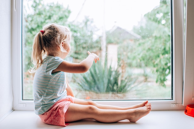 A gorgeous blonde little girl with ponytale staring out of the window on a wet, cold rainy summer day and showing somewhere with her finger
