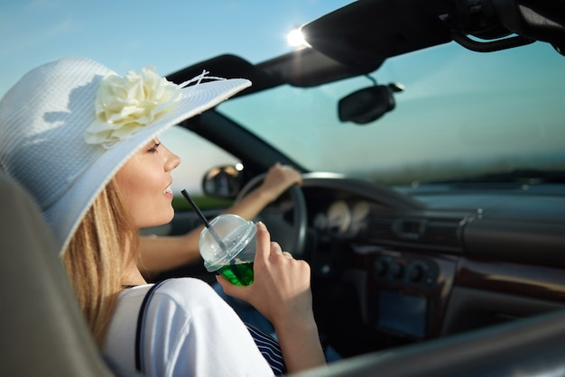 Gorgeous blonde sitting in luxurious cabriolet and holding lemonade glass.