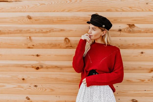 Splendida donna bionda con cappello nero e bel maglione rosso in posa teneramente sulla parete di legno. affascinante ragazza che gode di una calda giornata autunnale all'esterno.