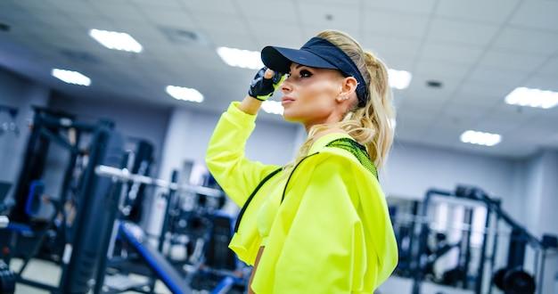 ゴージャスな金髪の女性がスポーツ用品でポーズをとっています。彼女は明るいスポーツウェアと帽子をかぶっています。