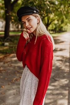 秋の公園でポーズをとるゴージャスなブロンドの女性。赤いセーターと白いスカートと素敵な黒い帽子をかぶっている美しい少女。