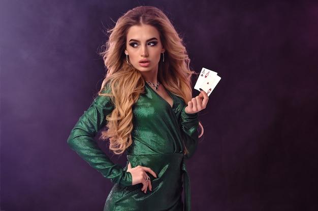 Великолепная блондинка с ярким макияжем, в зеленом стильном платье и украшениях. она показывает две игральные карты, положив руку на талию,
