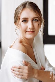 화려한 신부. 창에서 흰 가운에 긴 머리를 가진 아름 다운 여자.