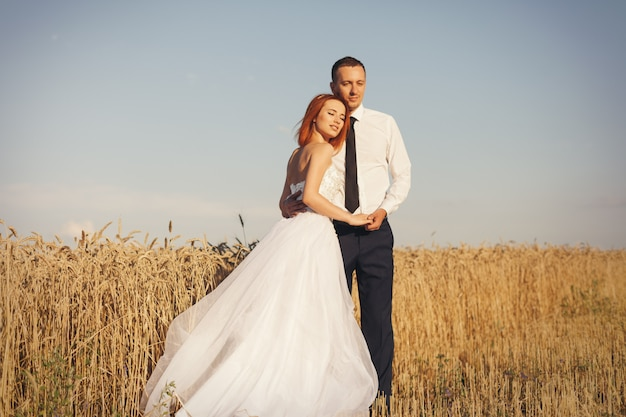 Gorgeous bride and groom in wheat field. happiness and marriage
