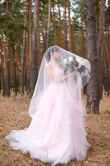Gorgeous bride in pink dress stands hidden under the veil in a forest