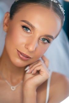 웨딩 화이트 베일과 아침 시간 동안 포즈 럭셔리 액세서리에 화려한 신부. 그녀의 인생에서 가장 행복한 하루를 준비하는 파란 눈을 가진 예쁜 여자.