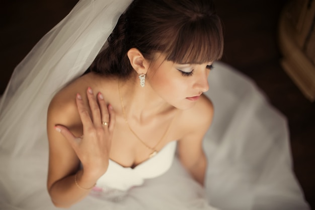 Gorgeous bride in wedding dress in luxury interior with diamond jewelry posing at home