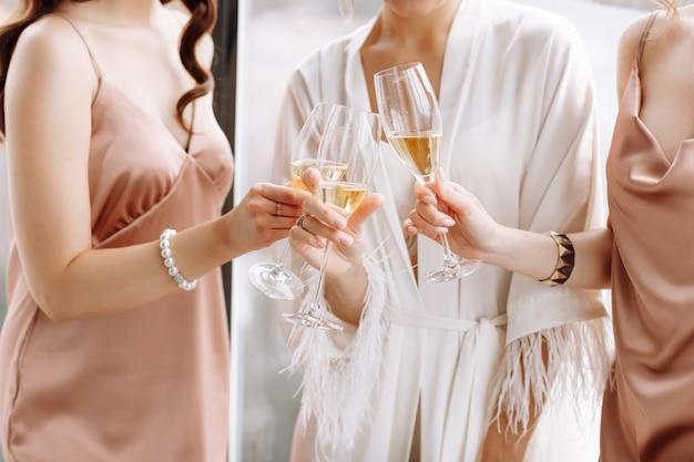 最高の花嫁介添人を持つゴージャスな花嫁は、大きな窓の近くのホテルの部屋でグラスを持ってシャンパンを飲んでいます。