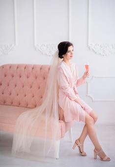 Великолепная невеста с бокалом розового шампанского сидит в розовом шелковом халате и вуалью